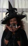 拿着水晶球的美丽的深色的巫婆 免版税库存图片