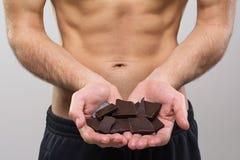拿着黑暗的巧克力片的年轻人适合的人 图库摄影