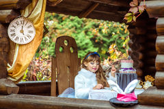 拿着轻松的事在匙子的一个小美丽的女孩的正面图在桌上 免版税库存图片