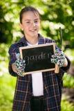拿着黑板和工具的从事园艺的手套的逗人喜爱的女孩 免版税库存图片