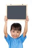 拿着黑板的亚裔矮小的中国女孩 免版税库存图片