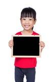 拿着黑板的亚裔矮小的中国女孩 免版税图库摄影