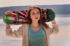 拿着滑板的俏丽的溜冰者女孩 库存照片