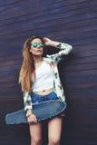 拿着滑板的偶然穿戴的女性行家,当站立在木墙壁背景的她在夏天时 免版税库存图片