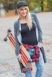 拿着滑板的凉快的俏丽的妇女 库存图片