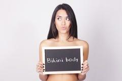 拿着黑板的少妇说比基尼泳装身体 免版税库存照片