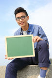 拿着黑板的愉快的人 库存照片