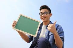 拿着黑板的愉快的人 免版税库存图片