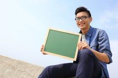 拿着黑板的愉快的人 免版税库存照片