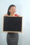 拿着黑板的愉快的逗人喜爱的微笑的成功的女实业家我 免版税库存图片