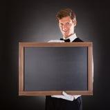 拿着黑板的男性侍者 免版税库存照片