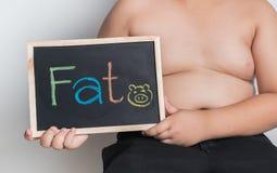 拿着黑板的肥胖肥胖男孩 免版税库存照片