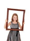 拿着画框的俏丽的女孩 免版税库存照片