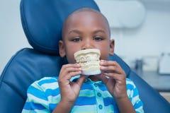 拿着嘴模型的微笑的男孩画象 免版税库存照片