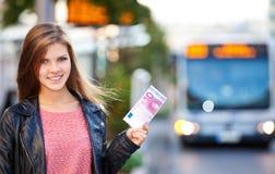 拿着10欧元的公共汽车站的女孩 库存图片