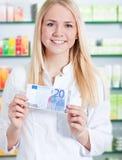 拿着20欧元的化学家的助理 免版税库存照片