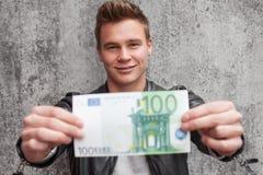 拿着100欧元笔记的年轻人 免版税库存图片