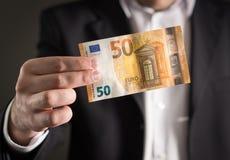 拿着50欧元钞票的衣服的商人 免版税图库摄影