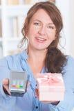 拿着付款终端和物品的卖主 免版税库存照片