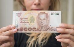 拿着1000泰铢笔记的妇女从ATM被撤出 免版税库存图片