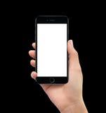 拿着黑流动聪明的电话大模型的被隔绝的人的手 免版税库存照片