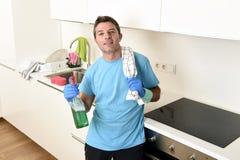 拿着洗涤的洗涤剂浪花瓶和布料在橡胶手套微笑的年轻愉快的人 图库摄影