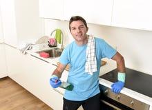 拿着洗涤的洗涤剂浪花瓶和布料在橡胶手套微笑的年轻愉快的人 免版税库存照片