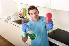 拿着洗涤的洗涤剂浪花瓶和海绵在手套微笑的年轻愉快的人确信 库存照片