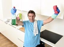拿着洗涤的洗涤剂浪花瓶和海绵在手套微笑的年轻愉快的人确信 免版税库存图片