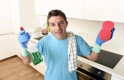 拿着洗涤的洗涤剂浪花瓶和海绵在手套微笑的年轻愉快的人确信 库存图片