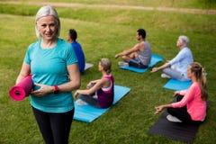 拿着锻炼席子的资深妇女画象,当执行瑜伽时的同事 免版税库存照片