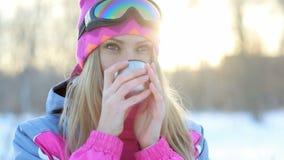 拿着从热水瓶的杯子在手上和饮料茶的妇女在冬天树背景多雪的分支  股票视频