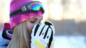 拿着从热水瓶的杯子在手上和饮料茶的妇女在冬天树背景多雪的分支  影视素材