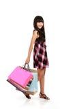 拿着购物侧视图妇女的袋子 库存照片