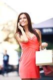 拿着购物袋和使用电话的愉快的妇女 免版税库存图片