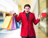 拿着购物袋和红色心脏的微笑的英俊的人 图库摄影