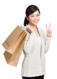 拿着购物袋和给胜利标志的妇女 库存照片