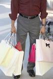 拿着购物袋的一个人的低部分  免版税库存图片