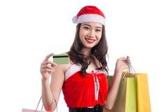 拿着购物袋的一名年轻微笑的妇女的画象在c前 库存图片