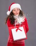 拿着购物袋的可爱的妇女吹雪 免版税库存照片