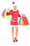拿着购物袋的圣诞老人服装的妇女 免版税图库摄影