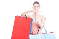 拿着购物袋的妇女做时间打手势 库存图片