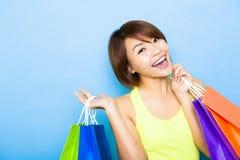 拿着购物袋的愉快的妇女在蓝色背景前 免版税库存照片