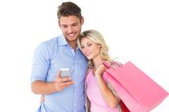 拿着购物袋的有吸引力的年轻夫妇看智能手机 免版税库存照片