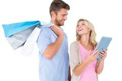拿着购物袋的有吸引力的年轻夫妇看片剂个人计算机 免版税库存图片