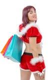 拿着购物袋的美丽的圣诞老人妇女 免版税库存照片