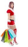 拿着购物袋的美丽的圣诞老人妇女 库存图片