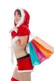 拿着购物袋的美丽的圣诞老人妇女 图库摄影