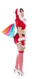 拿着购物袋的美丽的圣诞老人妇女 免版税库存图片