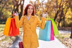 拿着购物袋的黄色外套的愉快的妇女 库存照片